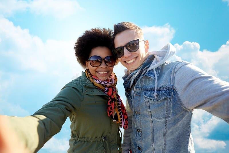 Happy teenage couple taking selfie over blue sky royalty free stock image