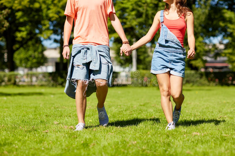 Happy teenage couple walking at summer park. Holidays, vacation, love and people concept - happy teenage couple walking in summer park royalty free stock photos