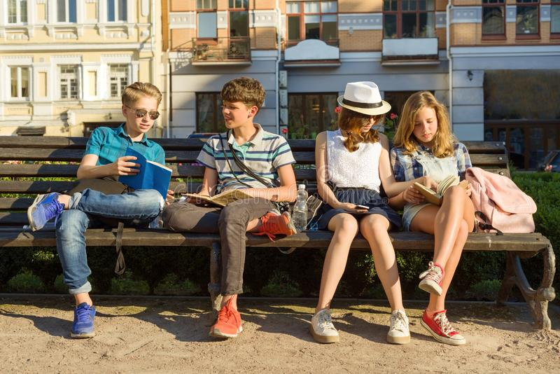 Happy 4 teenage friends or high school students are having fun, talking, reading phone, book. Friendship and people concept, city stock photo