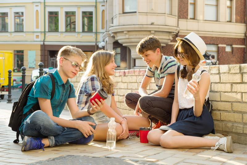 Happy 4 teenage friends or high school students are having fun, talking, reading phone, book. Friendship and people concept, city royalty free stock image
