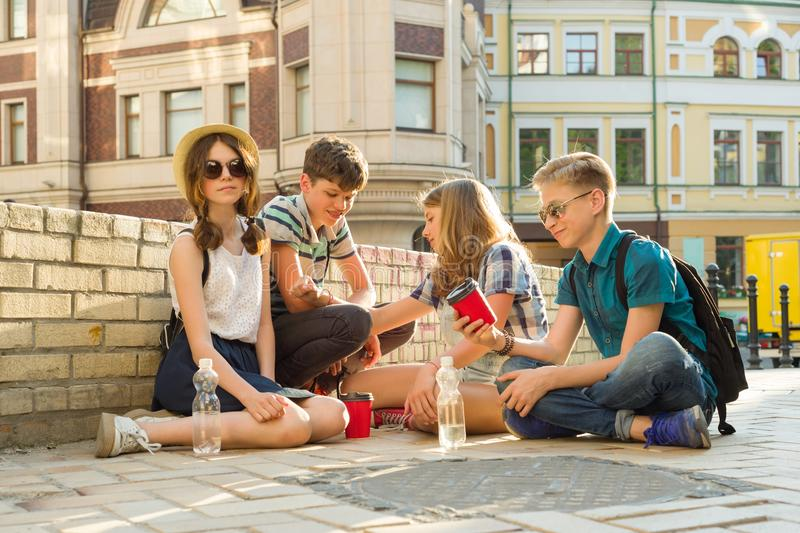 Happy 4 teenage friends or high school students are having fun, talking, reading phone, book. stock photos