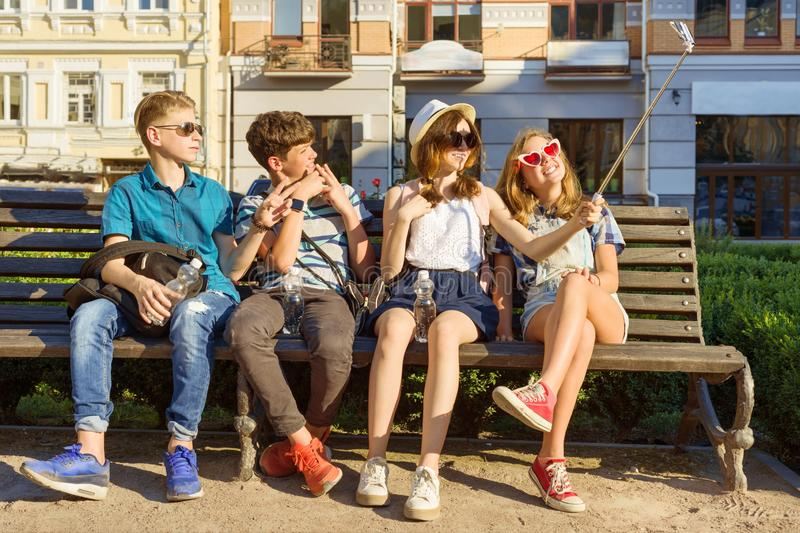 Happy 4 teenage friends or high school students are having fun, talking, reading phone, making selfie photo in city on bench. stock image