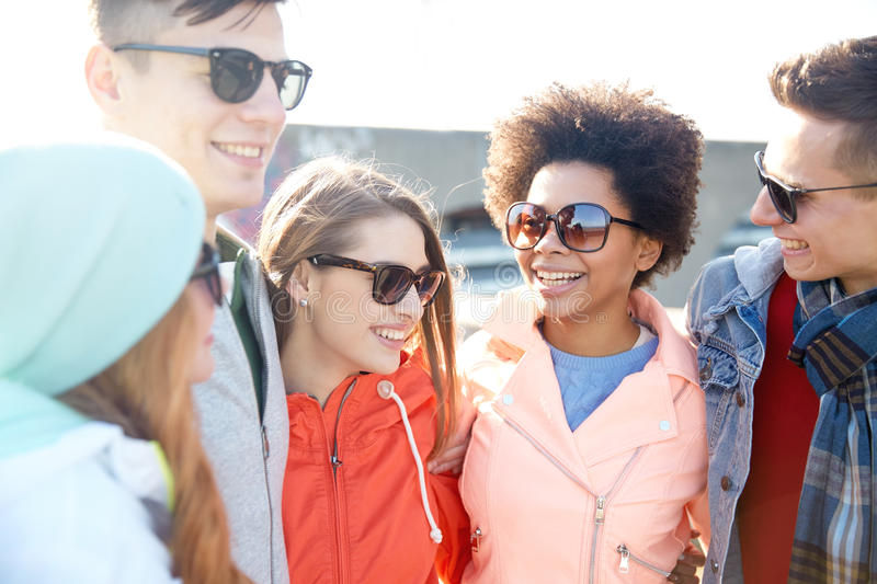 Happy teenage friends in shades talking on street. Tourism, travel, people, leisure and teenage concept - group of happy friends in sunglasses hugging and royalty free stock image
