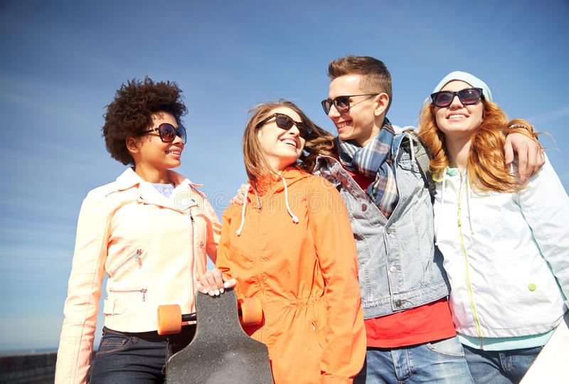 Happy teenage friends in shades talking on street. Tourism, travel, people, leisure and teenage concept - group of happy friends in sunglasses hugging and stock images