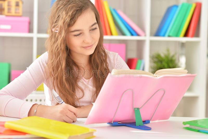 Portrait of happy teenage girl doing her homework stock images
