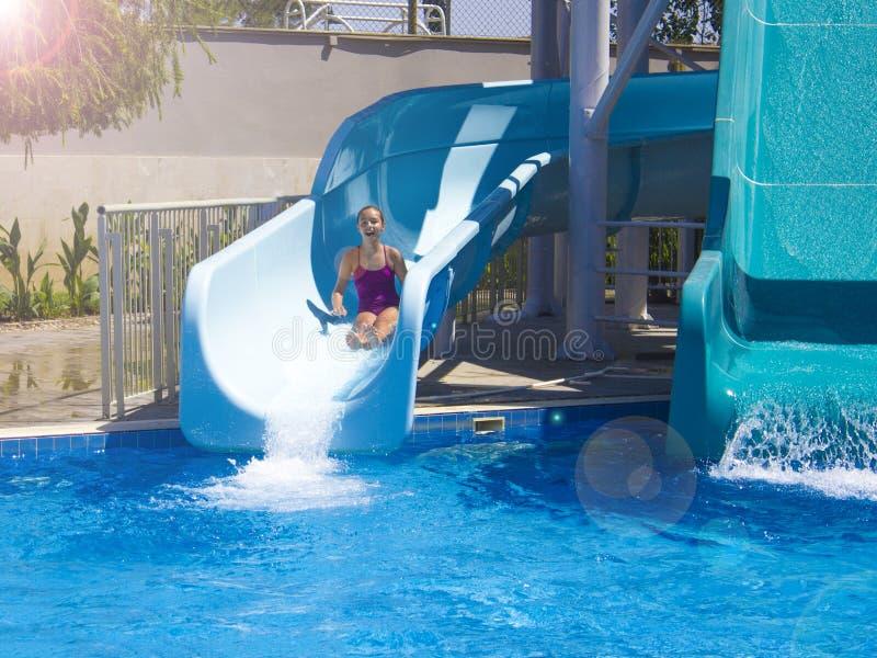 Happy teenage girl going down by water slide into the pool. Happy teenage girl going down by the water slide into the pool stock images