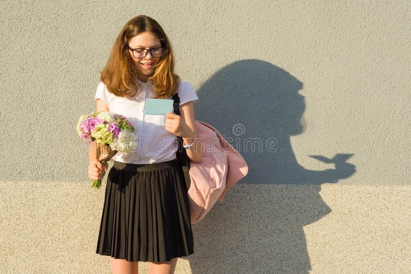 Happy teenage girl holding bouquet of flowers in her hands, reading card. Gray wall background, copy space. stock image