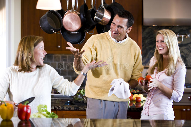 Happy teenage girl and parents chatting in kitchen royalty free stock photo