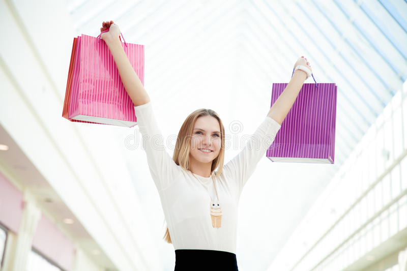 Happy teenage girl pleased with her purchases holding pink shopping bags royalty free stock photography