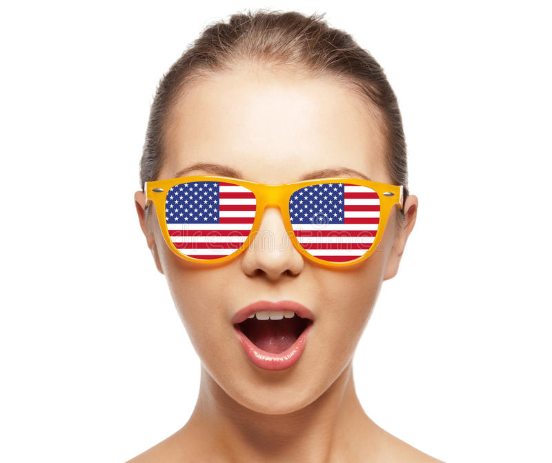 Happy teenage girl in shades with american flag stock photos