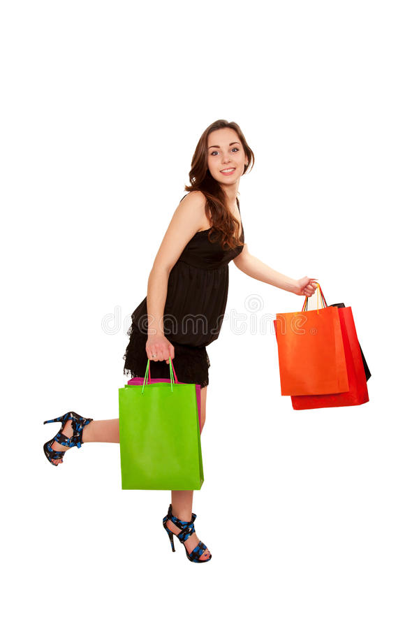 Happy teenage girl with shopping bags leaving the store. Side vi. Ew. Isolated on white background stock photo