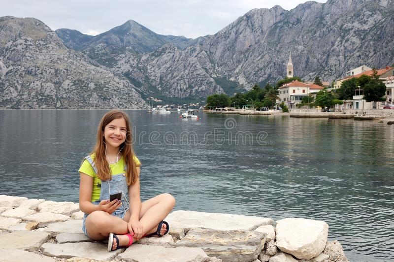 Teenage girl with smart phone on summer vacation Kotor bay Montenegro royalty free stock images