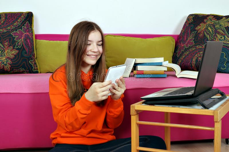 Teenage girl with tablet and laptop at home royalty free stock image