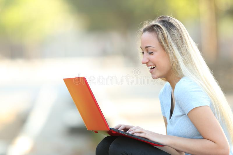 Happy teenage girl using a red laptop in a park royalty free stock photo
