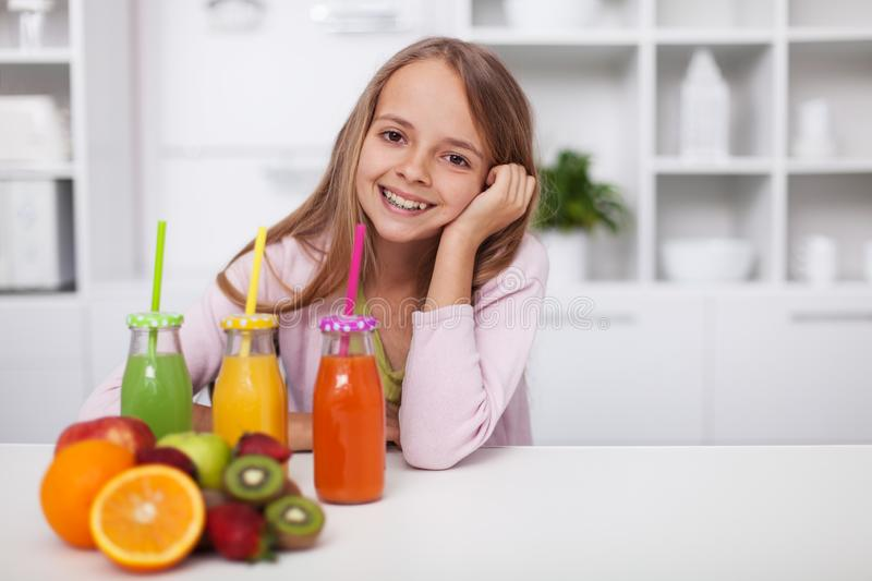Happy teenage girl with a variety of healthy fresh fruit juices royalty free stock image