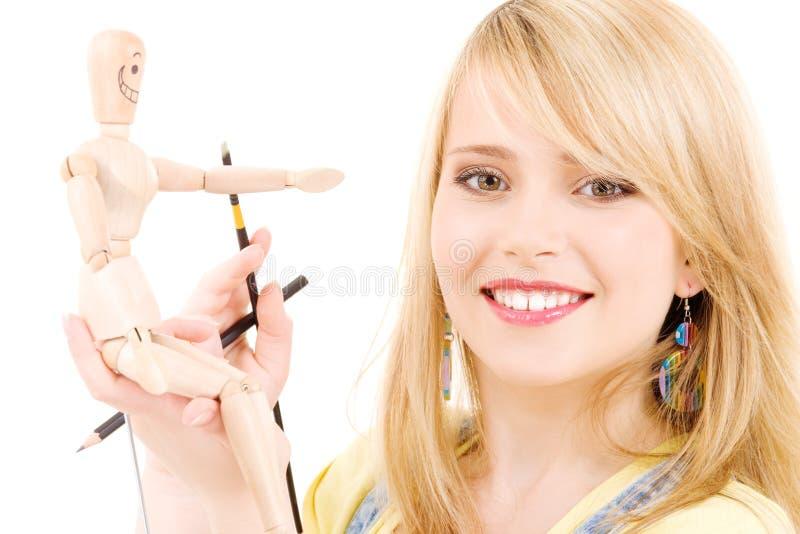Happy Teenage Girl With Wooden Model Dummy Stock Image