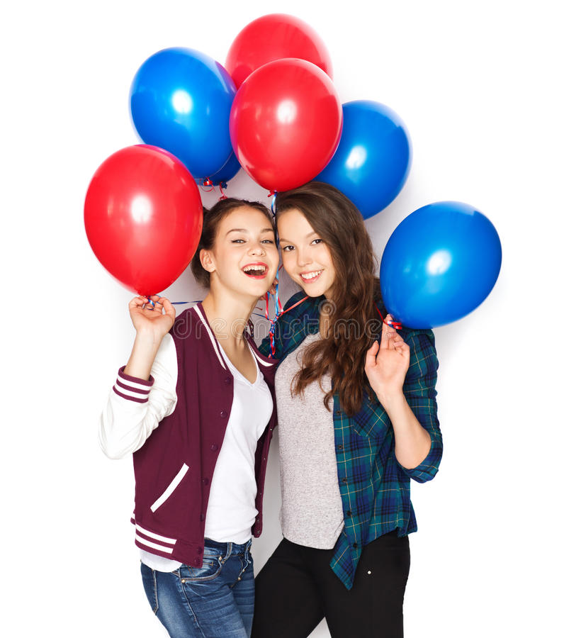 Happy teenage girls with helium balloons. People, friends, teens, holidays and party concept - happy smiling pretty teenage girls with helium balloons royalty free stock images