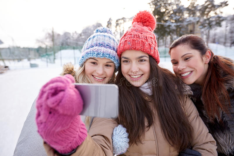 Happy teenage girls taking selfie with smartphone stock photos