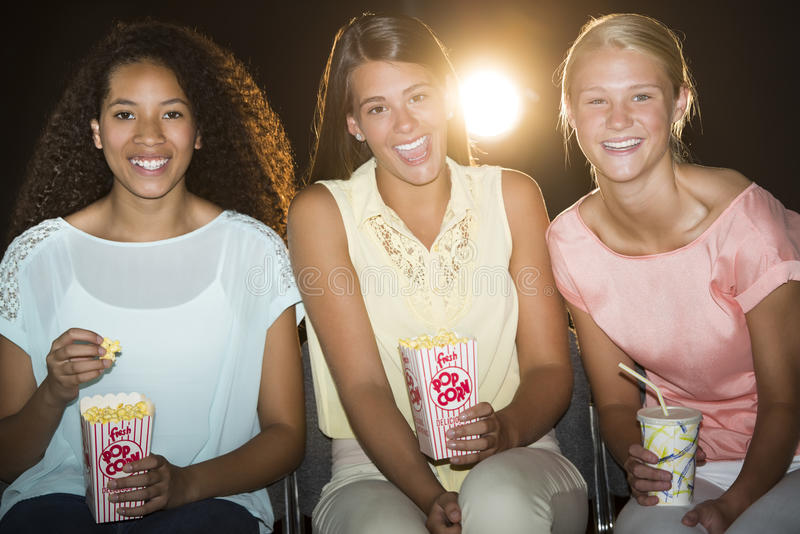 Happy Teenage Girls Watching Movie In Theater stock photos