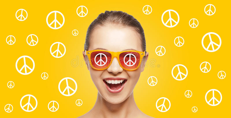 Happy teenage hippy girl in shades with peace sign. People, summer accessories and pop art concept - happy screaming teenage hippy girl in shades over yellow stock photography