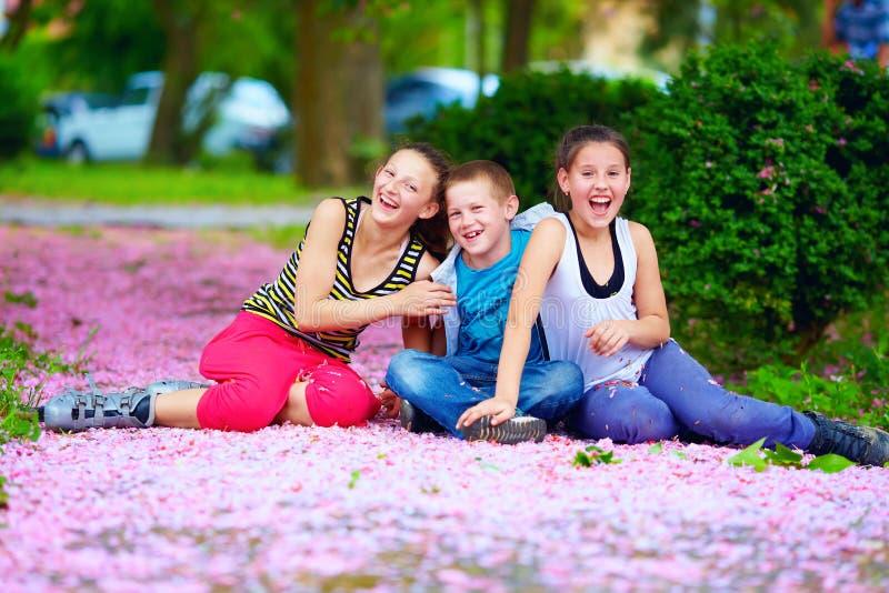 Happy teenage kids having fun in blooming park. Happy kids, teenagers having fun in blooming park, spring outdoors stock images
