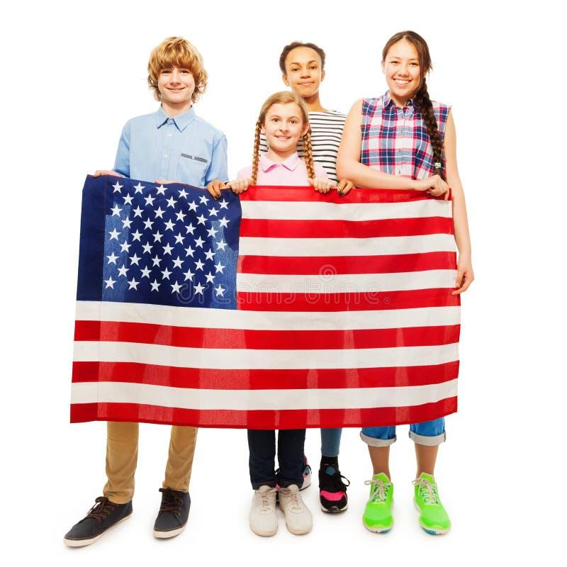 Happy teenage kids holding flag of United States. Four happy teenage kids holding American flag, standing behind it, on white background stock photography