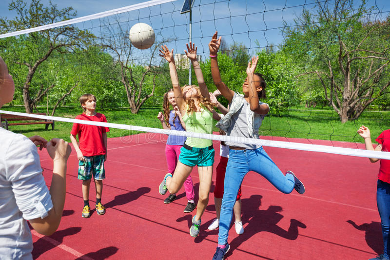 Happy teenage kids play volleyball outside. Happy teenage kids play together volleyball outside on the playground during summer sunny day royalty free stock photo