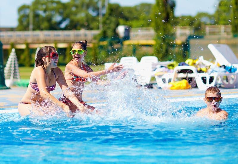 Happy teenage kids splashing the water in pool. Happy teenage kids splashing the water each other in pool royalty free stock photo