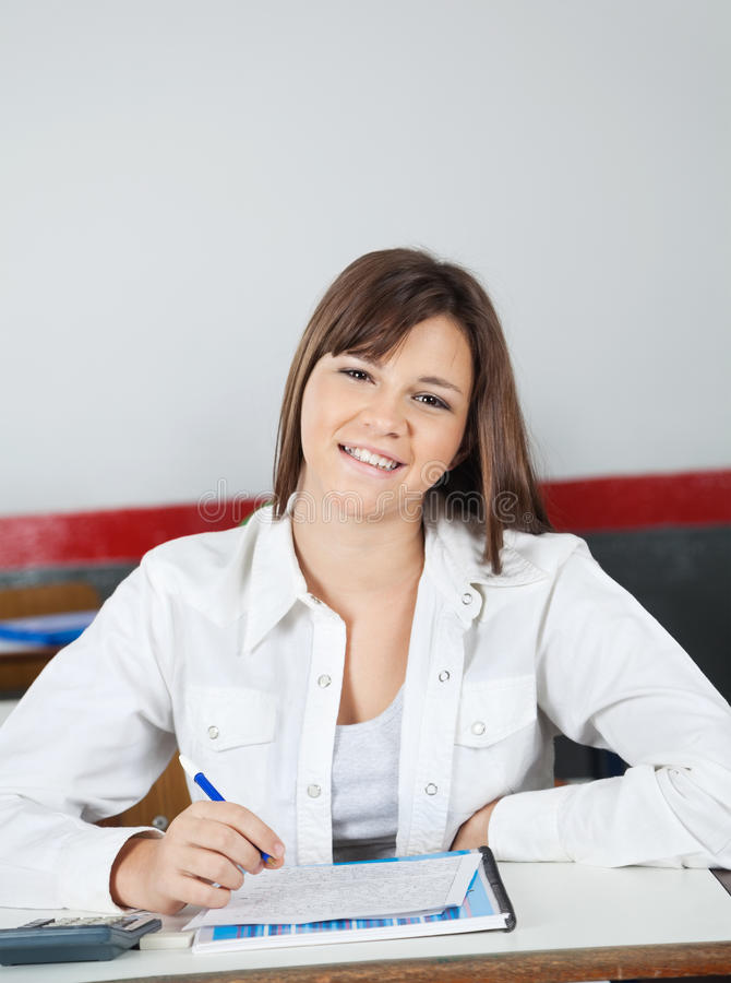Happy Teenage Schoolgirl Sitting At Desk royalty free stock images