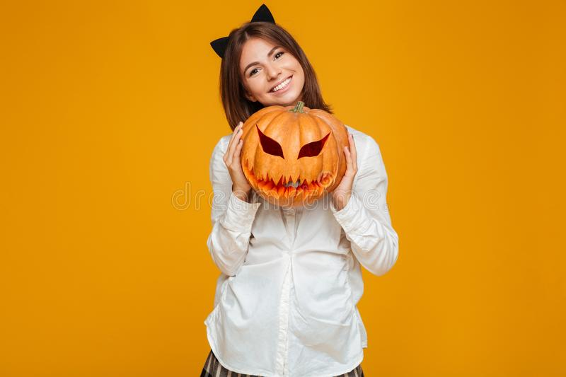 Happy teenage schoolgirl in uniform holding halloween pumpkin. And laughing isolated over orange background royalty free stock photography
