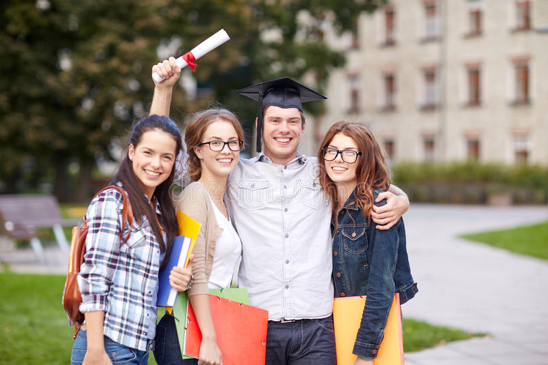 Happy teenage students with diploma and folders. Education, campus, friendship, graduation and people concept - group of happy teenage students with diploma stock images