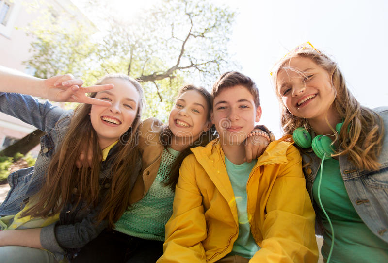 Happy teenage students or friends having fun stock image