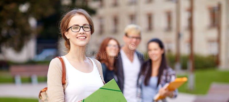 Happy teenage students with school folders royalty free stock photos
