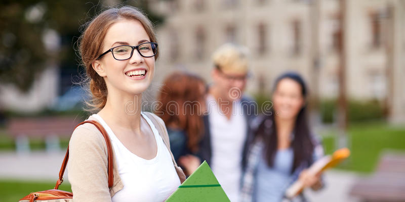 Happy teenage students with school folders royalty free stock photography