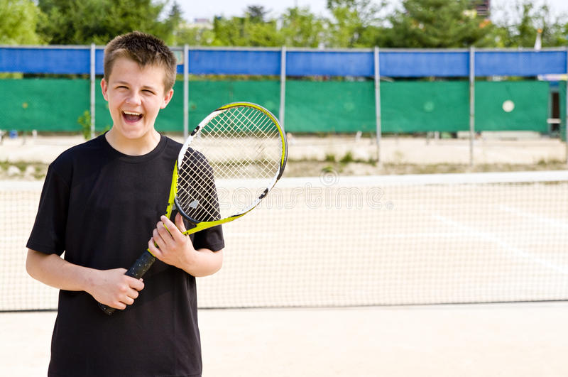 Happy teenage tennis player. Happy teenage boy at tennis court royalty free stock photo