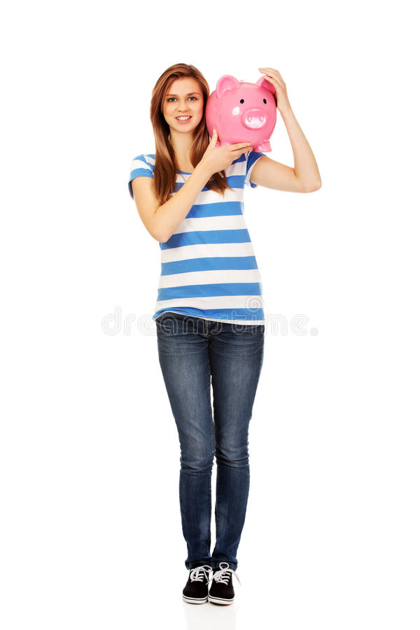 Happy teenage woman holding piggybank stock image