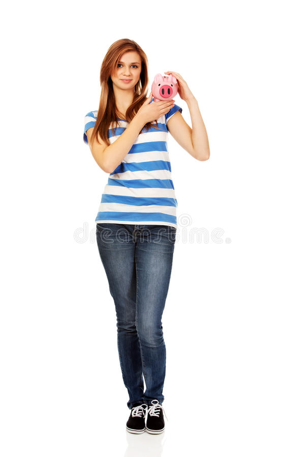 Happy teenage woman holding piggybank royalty free stock images