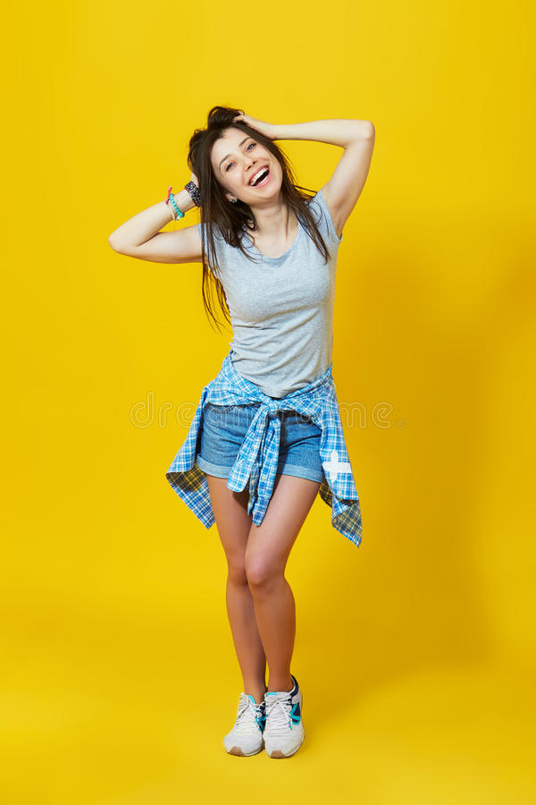Happy teenage woman over yellow background royalty free stock photo