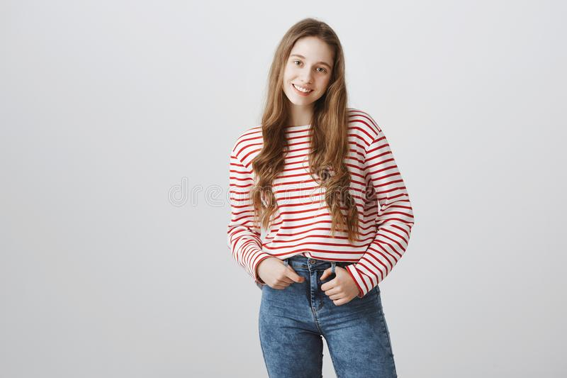 Happy teenage years. Portrait of young pretty blonde girl in trendy striped sweater holding hand in pocket and smiling royalty free stock photography