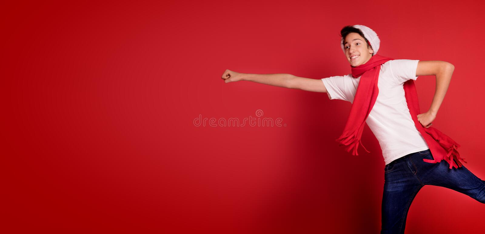 Teenager boy jumping in Santa Claus hat, smiling,posing in red background. Happy teenager boy jumping in Santa Claus hat, smiling,posing in red background stock photos