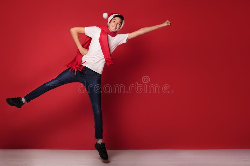 Teenager boy jumping in Santa Claus hat, smiling,posing in red background. Happy teenager boy jumping in Santa Claus hat, smiling,posing in red background royalty free stock photo