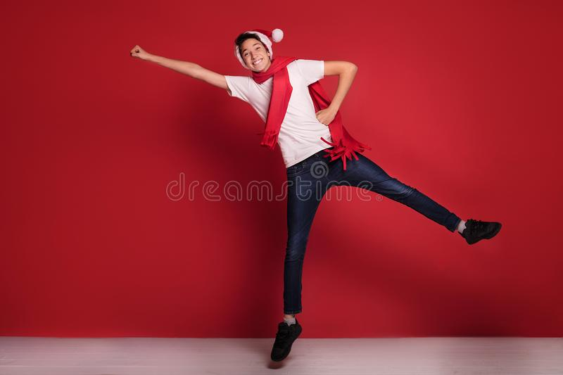 Teenager boy jumping in Santa Claus hat, smiling,posing in red background. Happy teenager boy jumping in Santa Claus hat, smiling,posing in red background royalty free stock photos