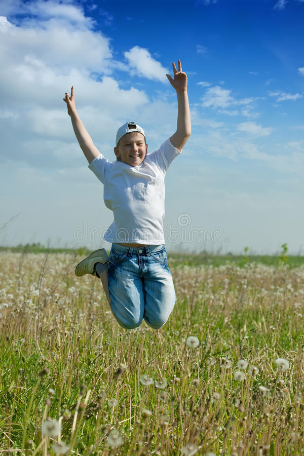 Happy teenager boy jumps at meadow. In summer stock photos