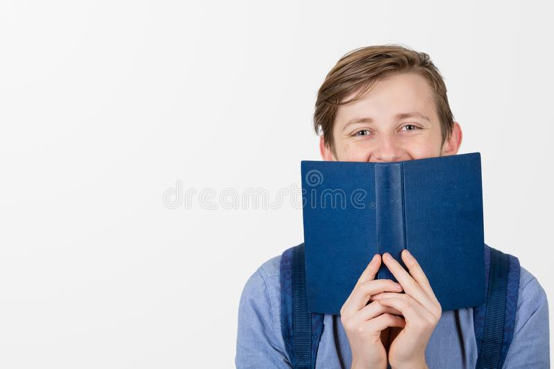 Happy teenager boy smiling covering half face with a opened blue book. Book lover. Ready to study hard. stock images