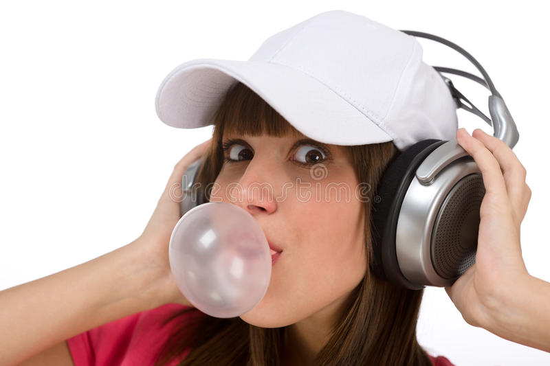 Happy teenager with bubble gum and headphones. Smiling female teenager enjoy music on white background, with headphones and bubble gum royalty free stock image