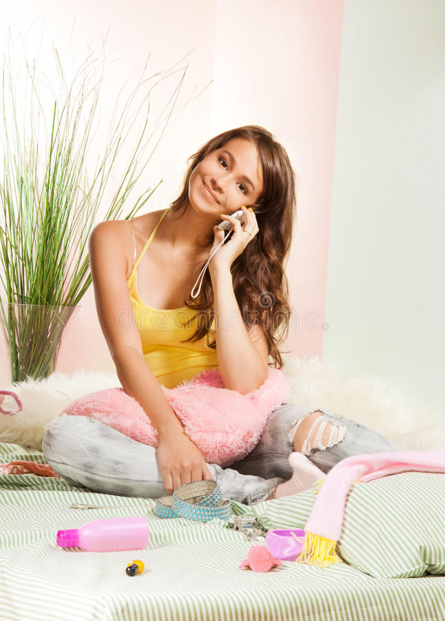 Happy teenager chatting on phone. Happy teenager chatting on cell phone with her mates sitting in bd stock images