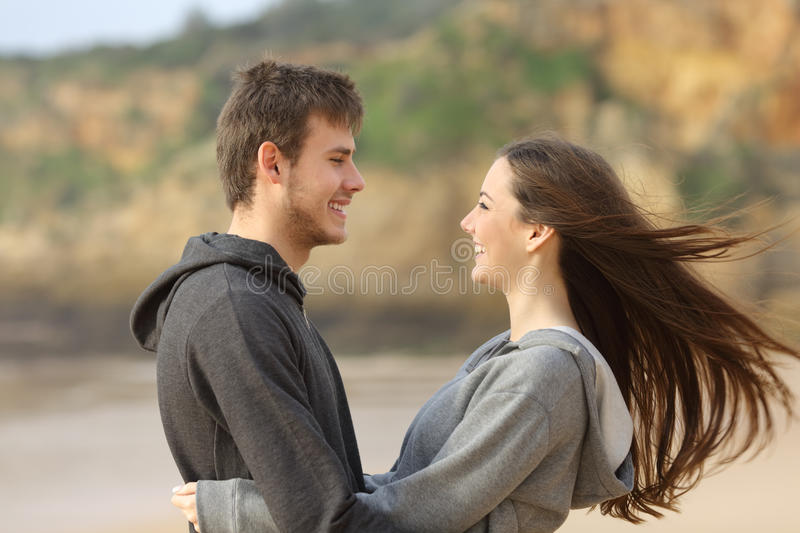 Happy teenager couple hugging and facing. Side view of happy teenager couple dating and flirting hugging and facing on the beach while the wind moves her hair stock photography