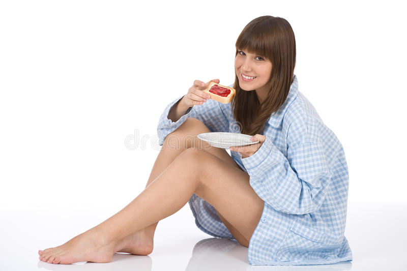 Happy teenager eating healthy toast for breakfast. Happy teenager in pajamas eating healthy toast for breakfast on white background royalty free stock image