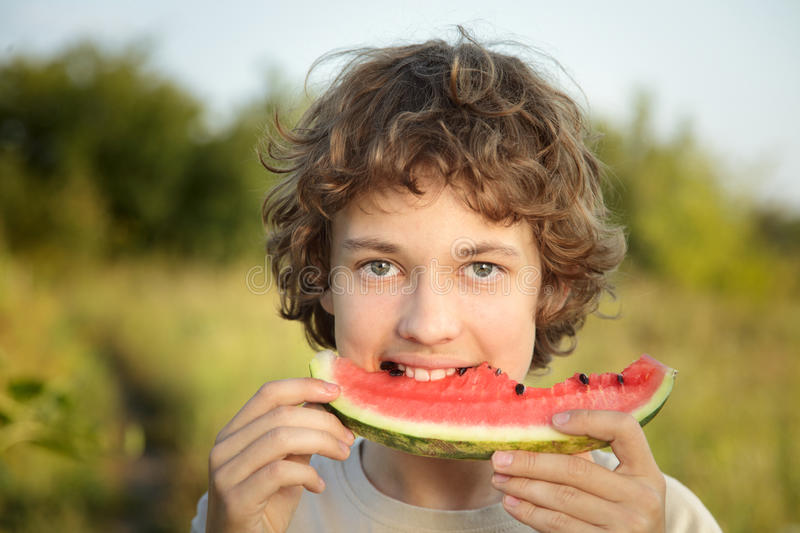 Happy teenager eating watermelon royalty free stock image
