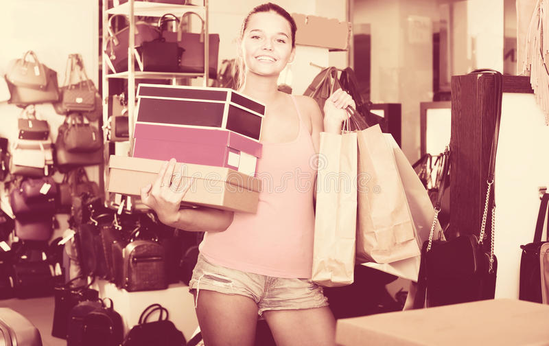 Happy teenager female holding boxes in shoes boutique. Happy teenager female holding boxes with chosen pairs in shoes boutique royalty free stock photo
